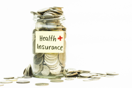 Jar with money labeled heath insurance
