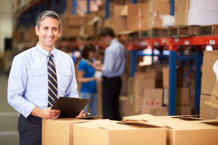 Man standing with clipboard in warehouse