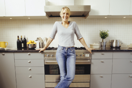 Woman leaning on kitchen counter smiling