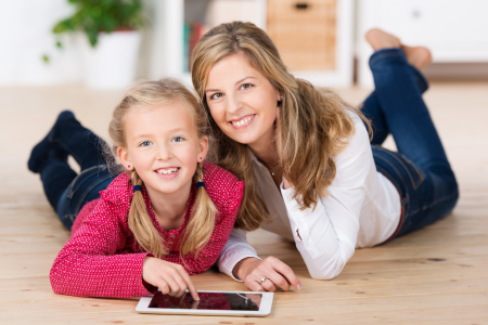 Mom and Daughter smiling playing on tablet