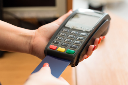 Person holding commercial debit card reader making a payment