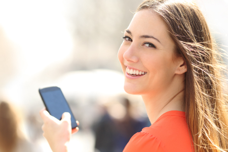 Young lady smiling holding phone
