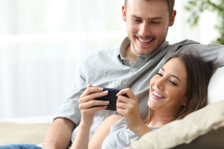 Man and Woman looking and smiling at cell phone