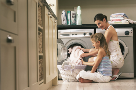 Daughter helping Mom empty clothes dryer