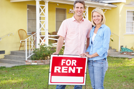Husband and wife standing in front of house with a for rent sign